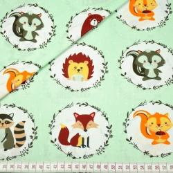 Bawełna zwierzątka w kołach na zielonym tle