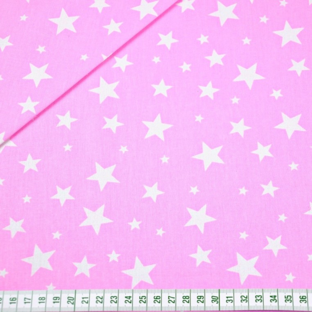 Tkanina w gwiazdki nowe małe i duże białe na różowym tle