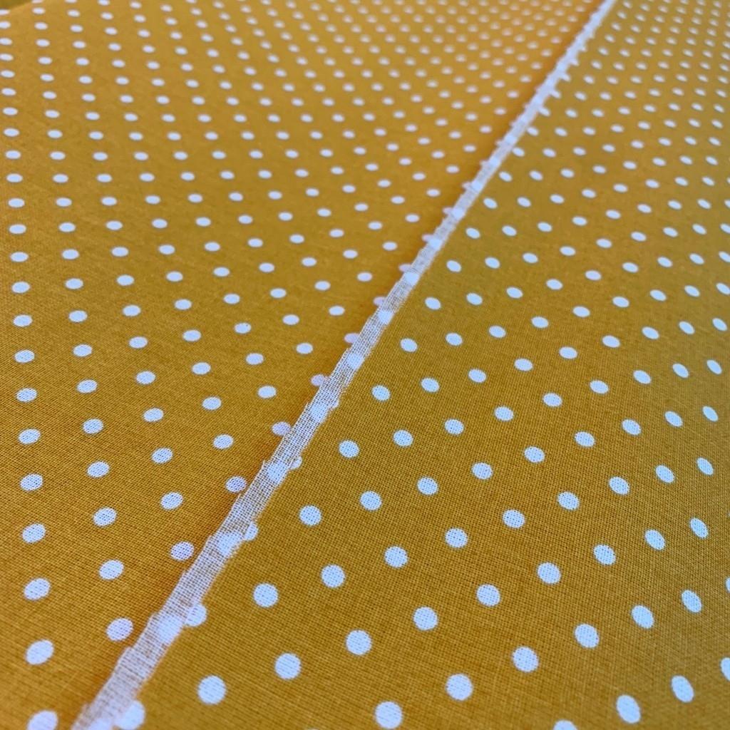 Tkanina w kropki białe na musztardowym tle