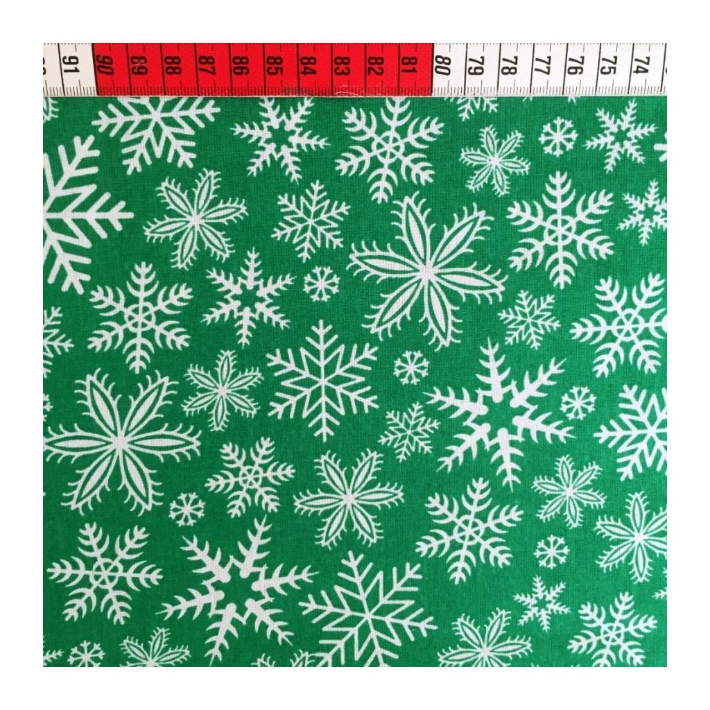 Tkanina w śnieżynki białe na zielonym tle